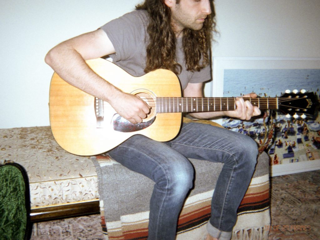 Ben Rabb, co-founder of and repeat, playing guitar as his first health ritual.